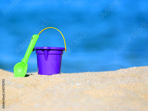bucket and shovel in sand on seashore