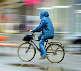 Cyclist on the city roadway in rainy day in motion blur