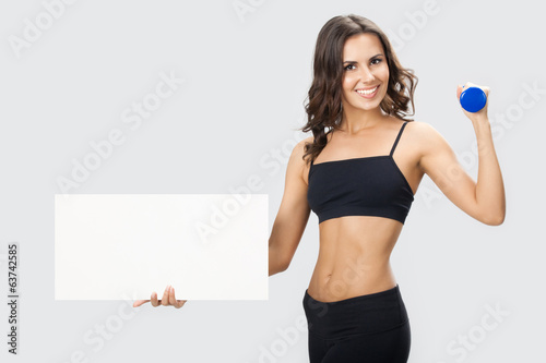 Woman in fitnesswear showing signboard, over grey