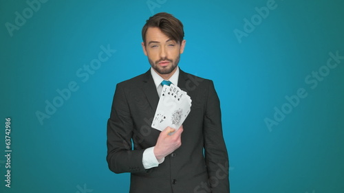 handsome businessman holding playing cards