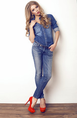 beautiful woman with blond hair in jeans posing at studio