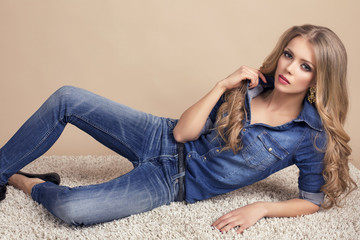 beautiful model with blond hair in jeans lying on the carpet
