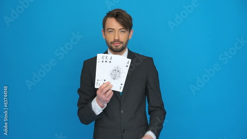 handsome business man holding playing cards