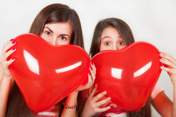 two girls with inflatable balloons in the form of hearts