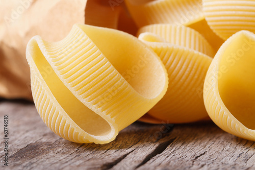 Raw Italian macaroni lumaconi scattered of paper packaging