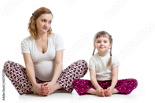 Young pregnant woman with little kid doing yoga exercises