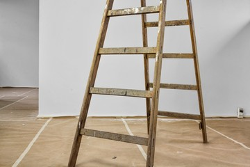 Wood ladder standing on a cardboard covered floor