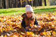 little girl sits on fallen leaves in autumn park