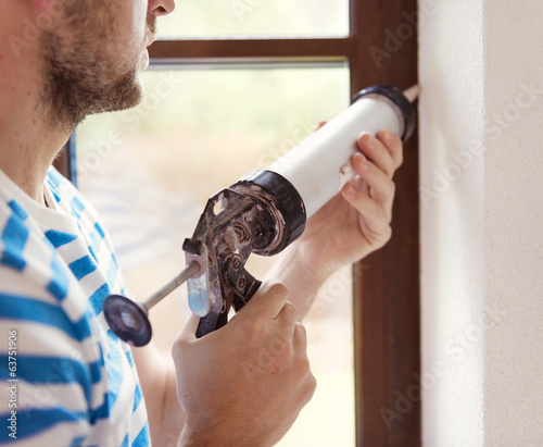 Man with caulking gun - 63751906