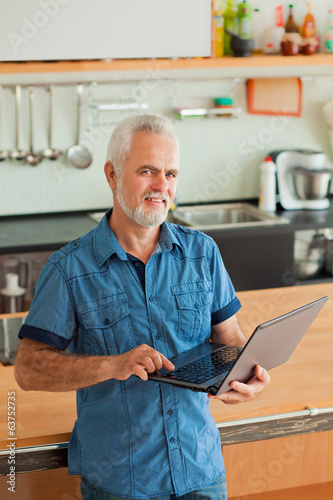 old man with notebook sitting at the kitchen