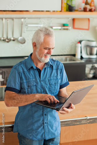 old man with notebook at the kitchen