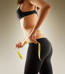 Girl measuring her waist with tape measure