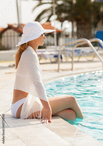 Beautiful woman enjoying and sitting on edge of the pool.