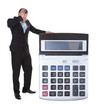Worried businessman viewing a large calculator
