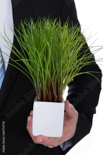 Businessman with a green plant in his pocket