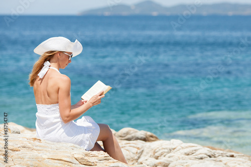 Beautiful woman reading book and relaxing on the beach.