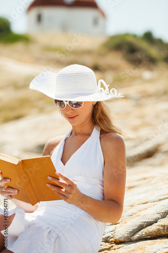 Beautiful Girl with a book sitting on the rock
