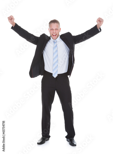 Young businessman in a suit standing cheering