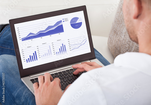 Businessman analyzing graphs on his laptop