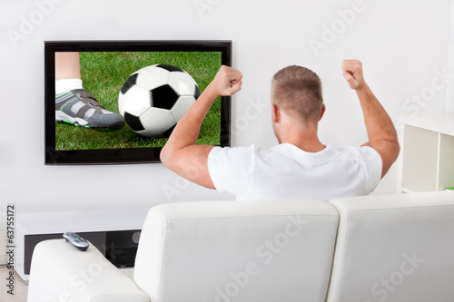 Excited soccer fan watching a game on television