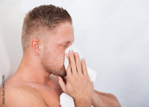 Man with a cold blowing his nose
