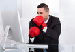 Scared Businessman With Boxing Gloves Looking At Computer