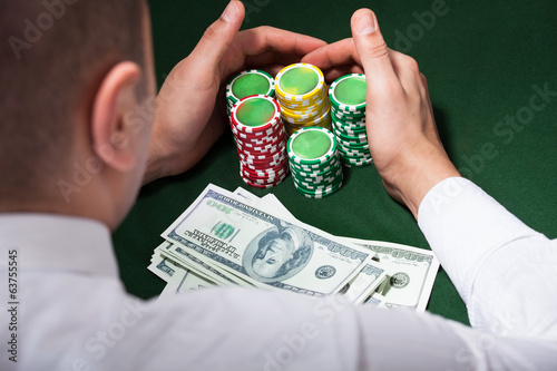 Man Scooping Up Dollars And Poker Chips