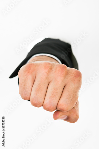 Businessman Punching Through White Wall