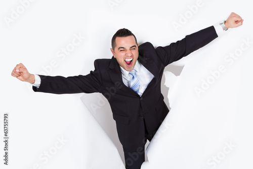 Successful Businessman Breaking Through White Wall