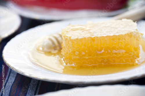 Honey and wooden stick at the background