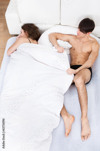 Man Pulling Duvet From Sleeping Woman In Bed