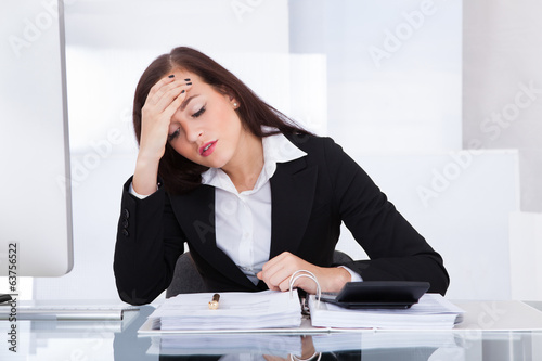 Tensed Businesswoman Calculating Tax