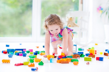 Funny blond toddler girl with curly hair sitting on a floor