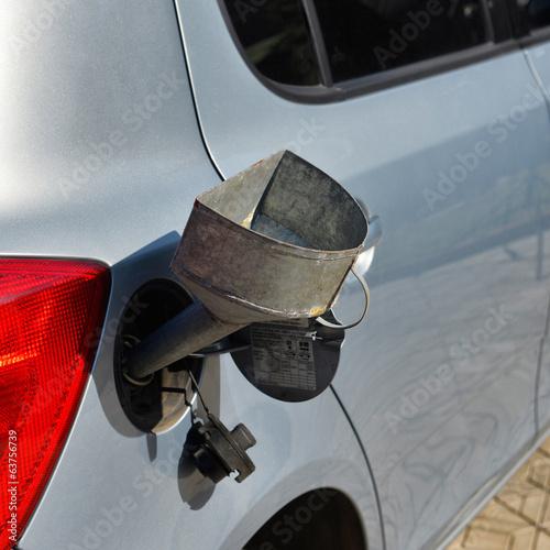 pouring fuel into the car gas tank