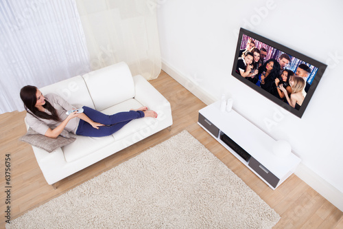 Woman Watching TV While Relaxing On Sofa