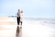 Happy loving middle aged couple walking on a beautiful beach