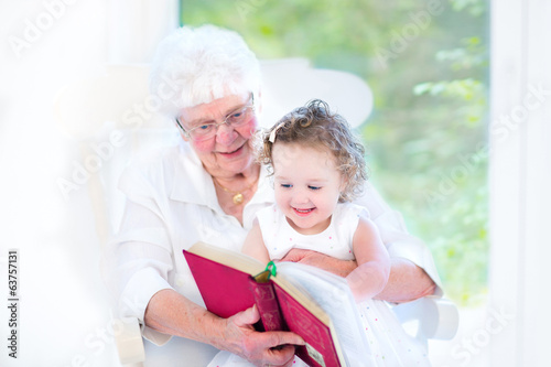 Beautiful senior lady reading a fairy tale book to grandchild
