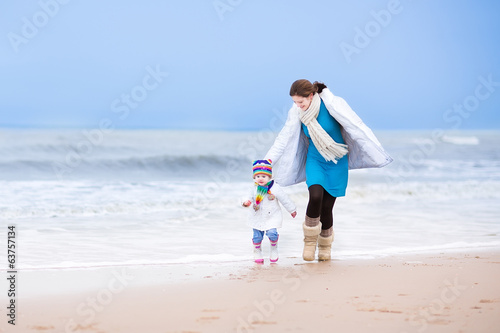 Young active mother and cute toddler daughter running on beach