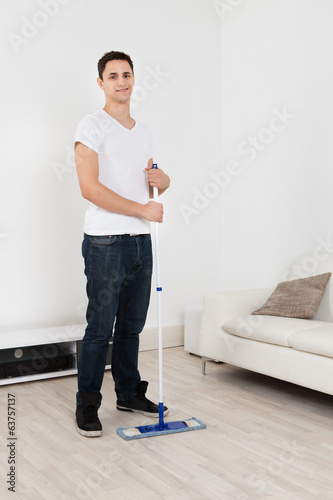 Young Man Mopping Floor At Home