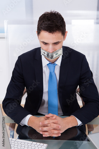 Businessman With Dollar Bill Covering Mouth