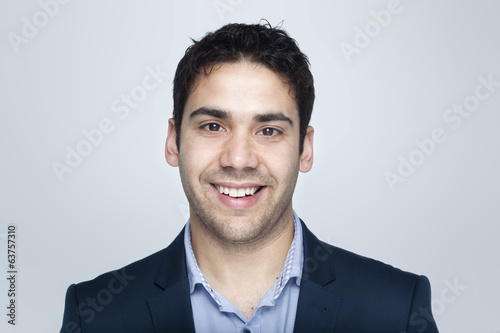 Confident business man smiling on grey background