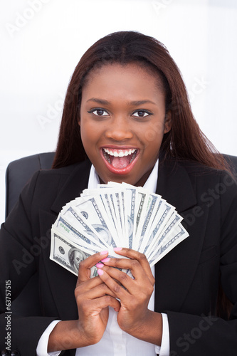 Businesswoman holding money fan in office