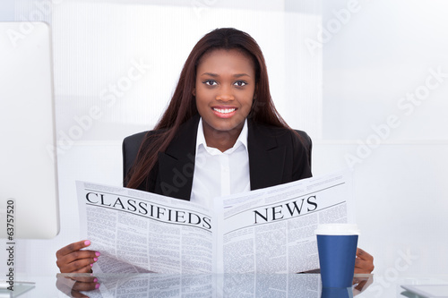 Businesswoman Reading Newspaper At Desk