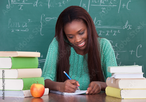 Female Teacher Writing In Book At Desk