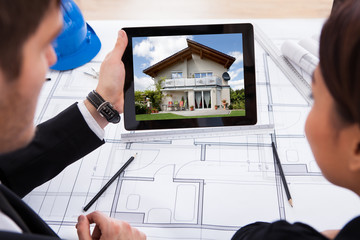 Architects With Digital Tablet Looking At House