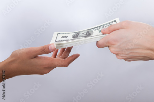 Businessman Giving Dollar Bills To Colleague