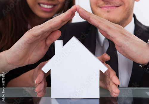 Business People Covering House Model