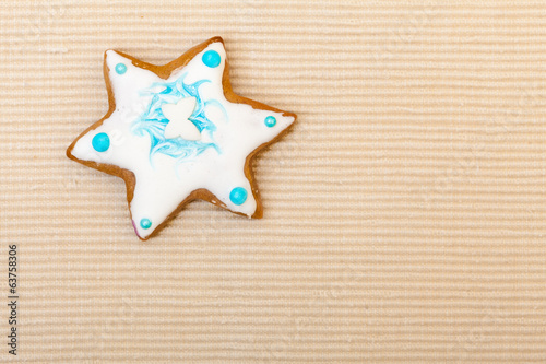 Christmas gingerbread cookie star with icing decoration on brown