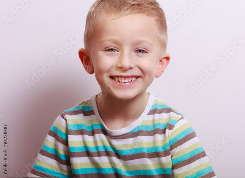 Portrait of happy laughing blond boy child kid at the table