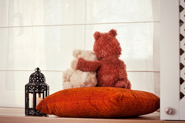 Two embracing loving teddy bears sitting on window-sill. Friends
